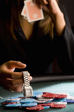hope indoors luck: Woman placing watch on pile of gambling chips on table, mid section LANG_EVOIMAGES