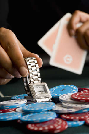 hope indoors luck: Woman placing watch on pile of gambling chips on table, close-up LANG_EVOIMAGES