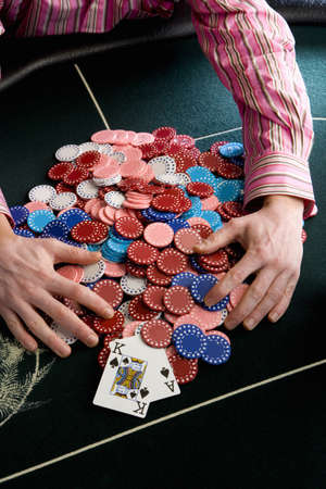 high stakes: Man collecting pile of gambling chips on table, mid section, elevated view