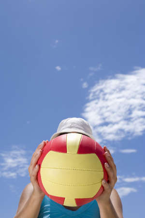 obscuring: Man obscuring face with ball outdoors, low angle view LANG_EVOIMAGES