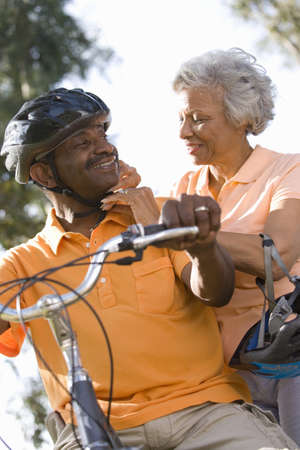 leis: Senior woman adjusting mans bicycle helmet, low angle view