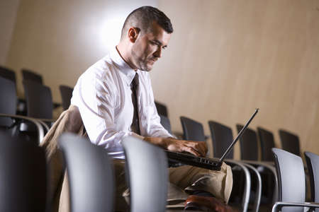 pres: Businessman typing on laptop in empty lecture hall