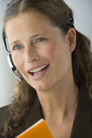 handsfree telephone: Businesswoman with hands-free telephone headset LANG_EVOIMAGES