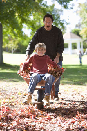 wheeling: Father wheeling son in wheelbarrow in autumn