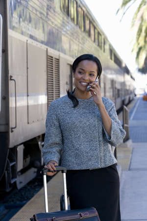 Businesswoman taking on cell phone at train station
