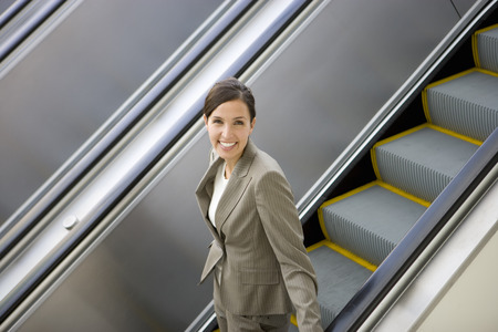 descending: Businesswoman riding on escalator