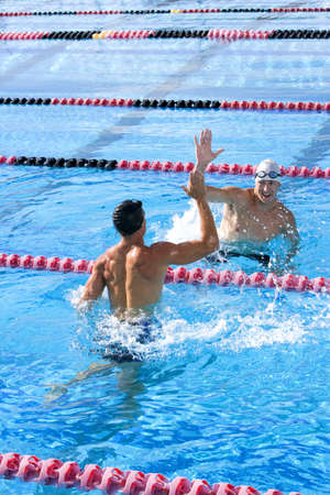 gentleman s: Two young male swimmers giving high-fives in swimming pool LANG_EVOIMAGES