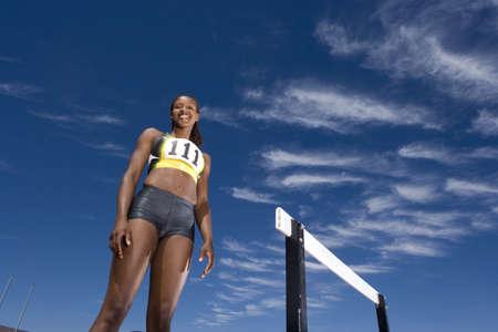 gratifying: African female athlete standing near hurdle