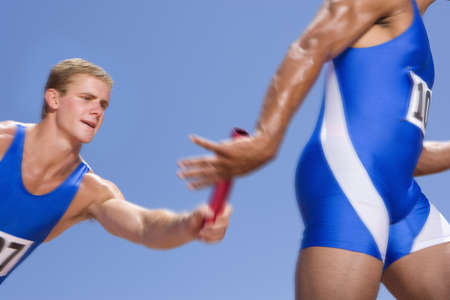 carrera de relevos: Atletas varones jóvenes que pasan la batuta carrera de relevos LANG_EVOIMAGES