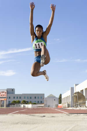 verticals: African female athlete mid-air during long jump
