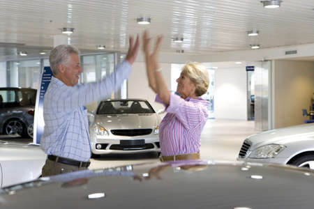 lavishly: Couple looking at new cars in showroom