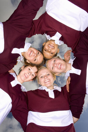 gratifying: Portrait of smiling teenage girls hugging in sports uniforms