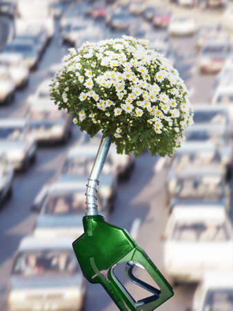 verticals: Green gas pump with blooming plant at end of nozzle and traffic in background