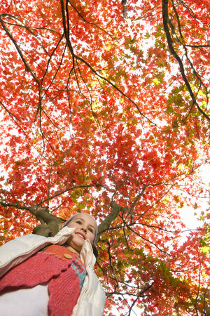 tetbury: Girl standing under tree with autumn leaves
