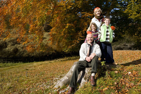 grandkids: Portrait of grandparents and grandkids in field with autumn leaves