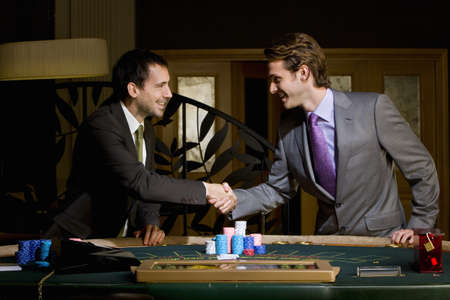 Two young men shaking hands over poker table, smiling, side view LANG_EVOIMAGES