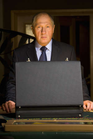 high stakes: Mature man with open briefcase at poker table, portrait