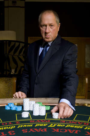 high stakes: Mature man placing gambling chips on poker table, portrait