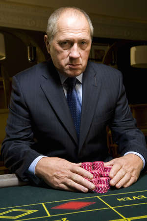 high stakes: Mature man with gambling chips at roulette table, portrait