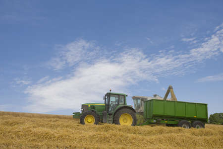 toils: Combine and tractor in barley field LANG_EVOIMAGES