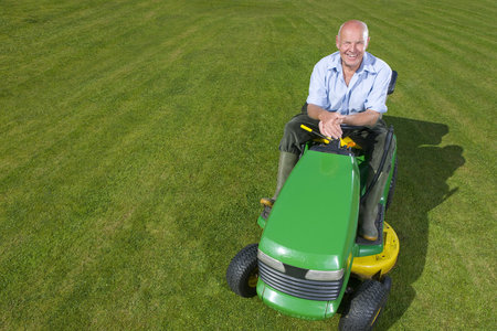 lawn mower: Portrait of man on riding lawn mower LANG_EVOIMAGES