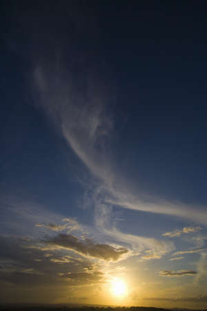 verticals: Sun setting in blue sky with clouds LANG_EVOIMAGES