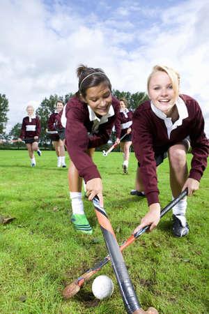 hockey sobre cesped: Retrato de la sonrisa adolescentes jugando hockey sobre hierba