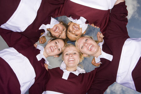 Portrait of teenage girls hugging in sports uniforms
