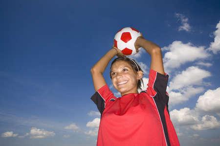 gratifying: Smiling teenage girl holding soccer ball overhead