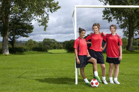 gratifying: Portrait of teenage soccer players standing at goal LANG_EVOIMAGES