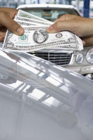lavishly: Hands exchanging one hundred dollar bills over luxury cars LANG_EVOIMAGES