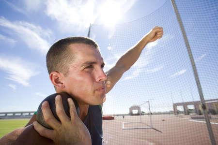 lanzamiento de bala: Hombre atleta que se prepara para lanzar la bola put tiro, vista de ángulo bajo (lens flare)