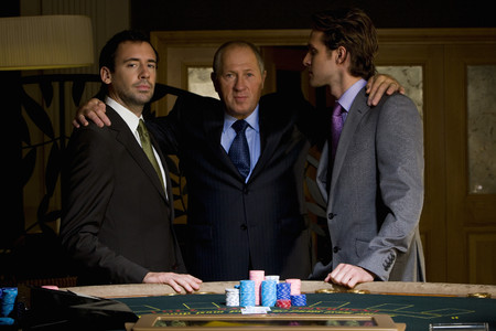 Mature man with arms around young men by poker table, portrait