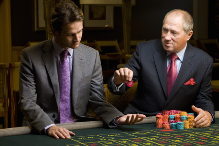 high stakes: Mature man with giving young man gambling chip at roulette table