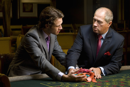 high stakes: Mature man giving young man pile of gambling chips at roulette table