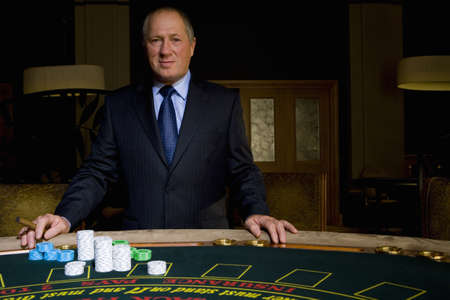 high stakes: Mature man with cigar at poker table, smiling, portrait