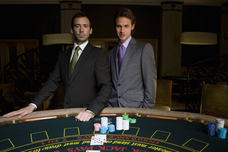 Two young men gambling at poker table, smiling, portrait LANG_EVOIMAGES