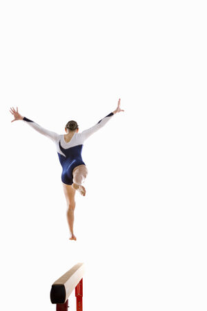balance beam: Female gymnast performing jump on balance beam, rear view LANG_EVOIMAGES