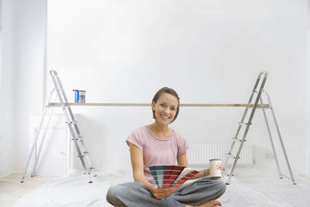 Smiling woman holding paint swatches in living room with ladders and wood plank in background