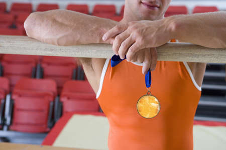 gold medal: Male gymnast with gold medal, arms on bar, mid section
