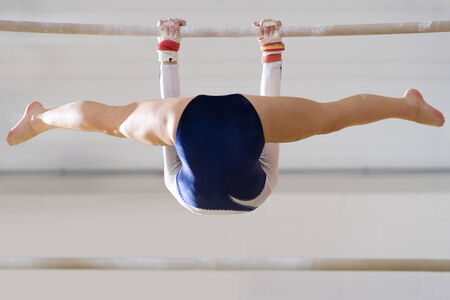angle bar: Female gymnast performing on bar, low angle view LANG_EVOIMAGES