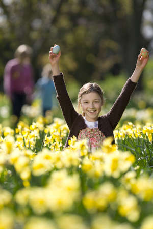 enviro: Young girl finding Easter eggs in field of daffodils