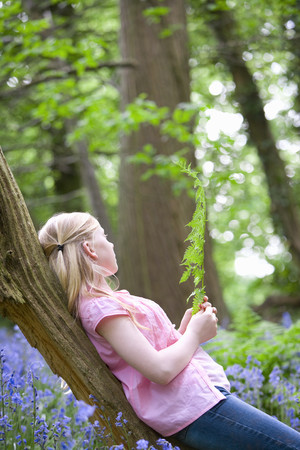 gals: Girl relaxing on tree trunk