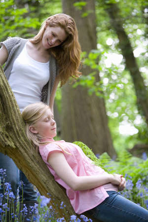 leant: Mother watching daughter relax on tree trunk in forest LANG_EVOIMAGES