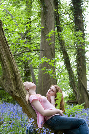leant: Mother and daughter relaxing on tree trunk in forest LANG_EVOIMAGES