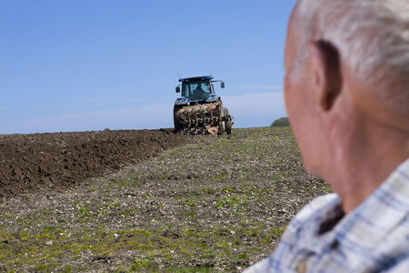 plough: Close up of farmer watching tractor and plough in field