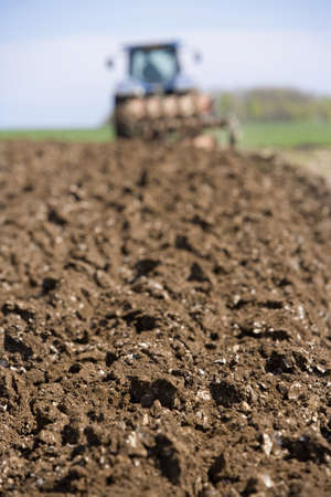 Close up of ploughed field with tractor and plough in background Stock Photo