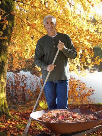 Man raking autumn leaves at edge of lake Stock Photo