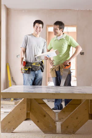 Smiling men with tools next to sawhorse LANG_EVOIMAGES