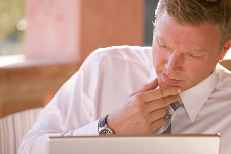 pat down: Close up of pensive businessman using laptop LANG_EVOIMAGES